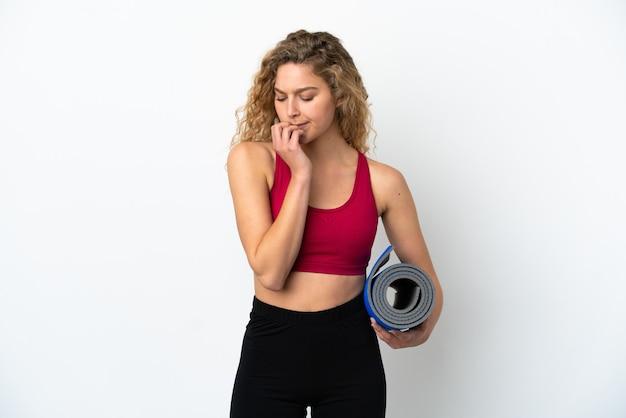 Jonge blonde sportvrouw die naar yogalessen gaat terwijl ze een mat vasthoudt die op een witte achtergrond wordt geïsoleerd en twijfelt
