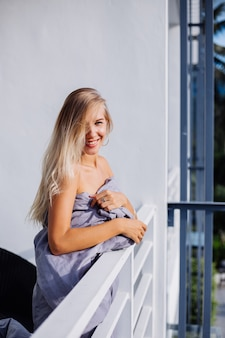 Jonge blonde stijlvolle europese vrouw in deken op tropisch balkon ontmoet zonsopgang in de ochtend.