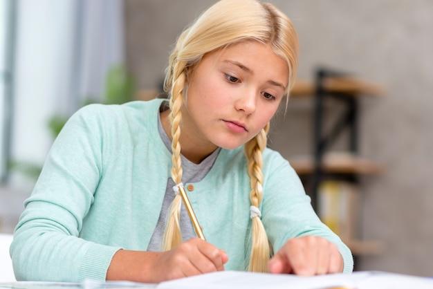 Jonge blonde student die aantekeningen maakt