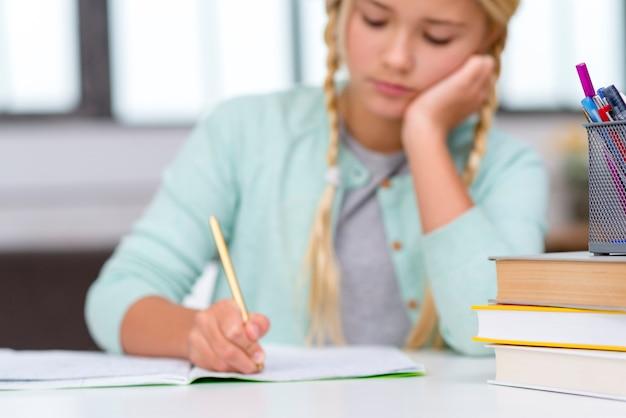 Jonge blonde student die binnen schrijft