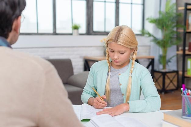Jonge blonde student die van haar privé-leraar leert