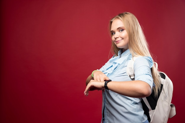 Jonge blonde student vrouw gaat terug naar school en controleert de tijd op haar horloge.