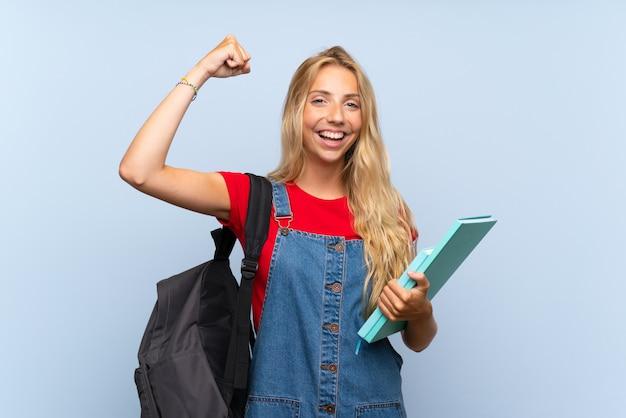 Jonge blonde studentenvrouw die over geïsoleerde blauwe muur een overwinning vieren