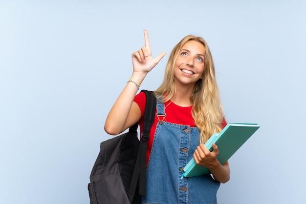 Jonge blonde studentenvrouw die over geïsoleerde blauwe muur met de wijsvinger een groot idee richten