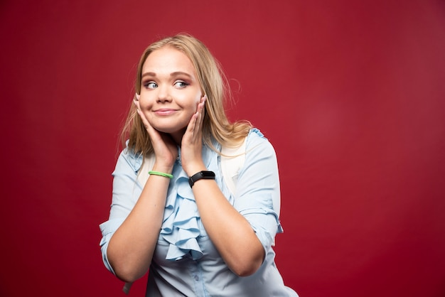 Jonge blonde studentenvrouw gaat terug naar school en voelt zich heerlijk en gelukkig.
