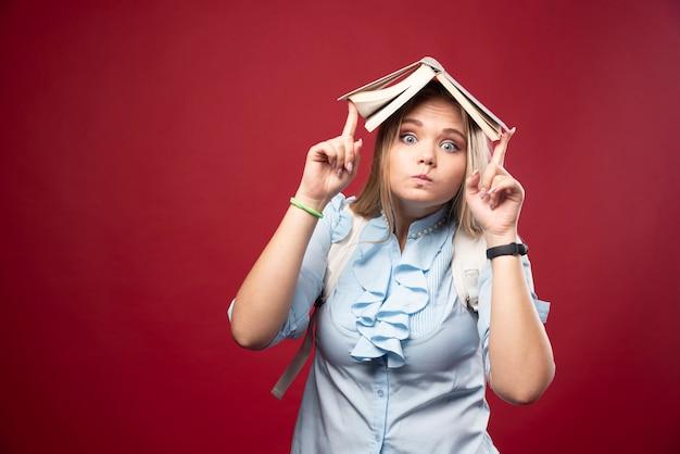 Jonge blonde studentenvrouw houdt haar boek bij haar hoofd en ziet er moe en verward uit.