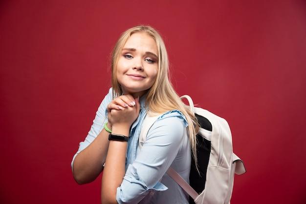 Jonge blonde studentenvrouw met haar rugzak gaat terug naar school en voelt zich heerlijk en gelukkig.