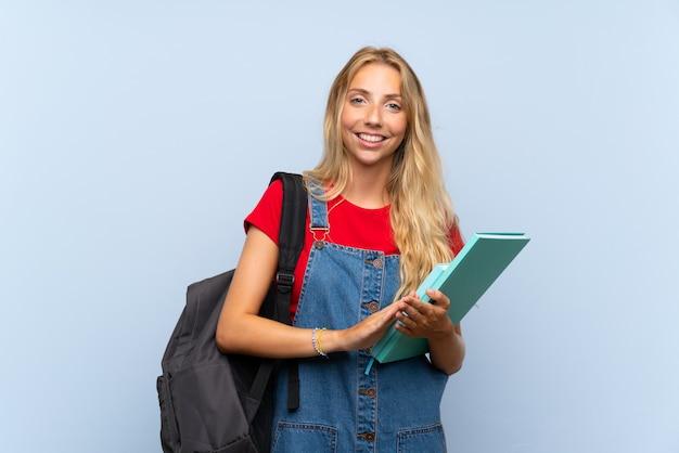 Jonge blonde studentenvrouw over het geïsoleerde blauwe muur toejuichen
