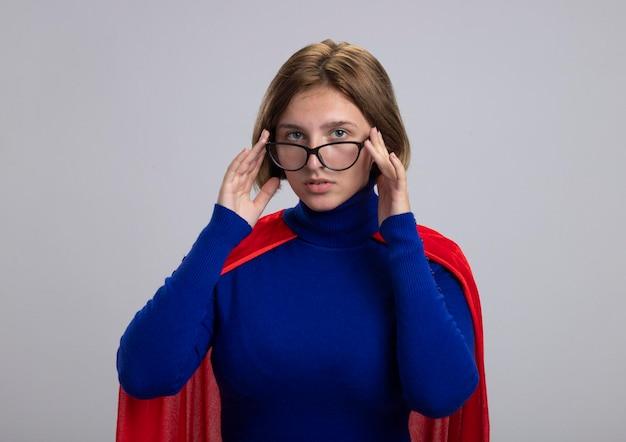 Jonge blonde superheld vrouw in rode cape bril kijken voorzijde aanraken van glazen geïsoleerd op een witte muur