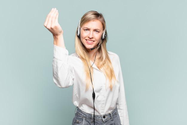 Jonge blonde telemarketeervrouw die capice of geldgebaar maakt en u vertelt om uw schulden te betalen!