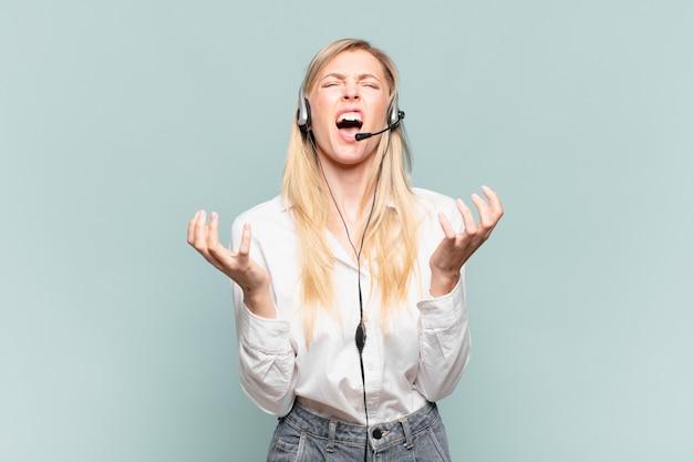 Jonge blonde telemarketeervrouw die er wanhopig en gefrustreerd, gestrest, ongelukkig en geïrriteerd uitziet, schreeuwend en schreeuwend