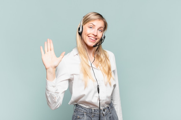 Jonge blonde telemarketeervrouw die gelukkig en opgewekt glimlacht, hand zwaait, u verwelkomt en begroet, of afscheid neemt