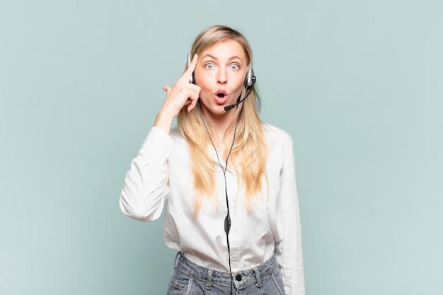 Jonge blonde telemarketeervrouw die verrast, met open mond, geschokt kijkt en een nieuwe gedachte, idee of concept realiseert