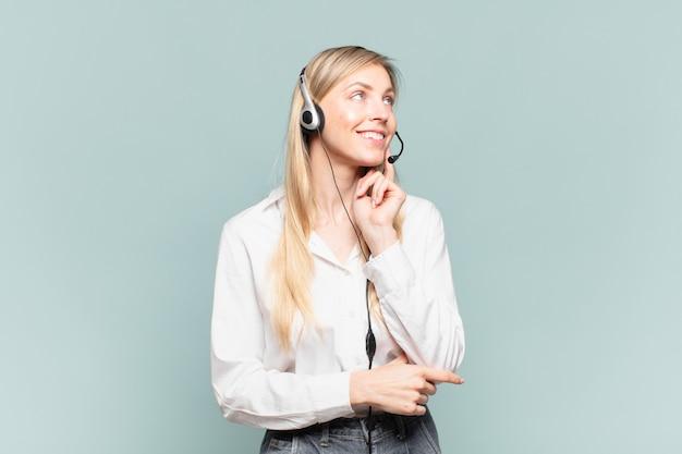 Jonge blonde telemarketeervrouw die vrolijk lacht en dagdroomt of twijfelt, opzij kijkend