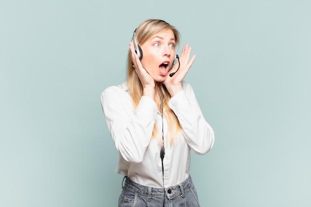Jonge blonde telemarketeervrouw die zich gelukkig, opgewonden en verrast voelt, opzij kijkend met beide handen op het gezicht