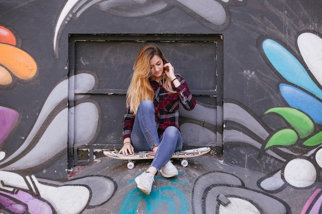 Jonge blonde tiener met een skateboard in een graffitimuur.