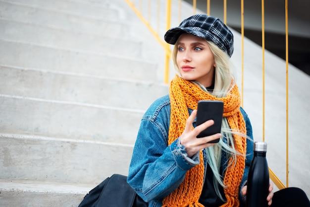 Jonge blonde tienermeisje met smartphone in de hand, gekleed in een blauwe spijkerjasje met oranje sjaal en geruite pet. op de muur van asfalterende grijze trappen.