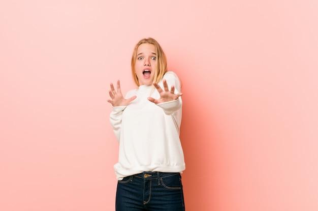 Jonge blonde tienervrouw die wordt geschokt wegens een dreigend gevaar