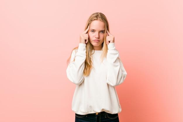 Jonge blonde tienervrouw die zich op een taak concentreerde, die wijsvingers hoofd houdt.