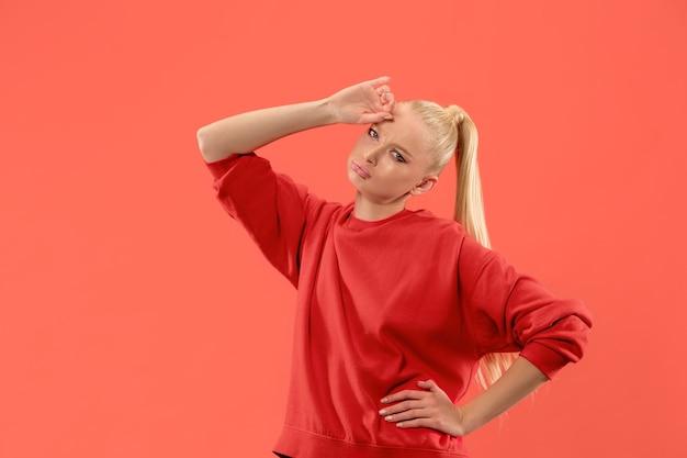 Jonge blonde vermoeide vrouw op koraalachtergrond