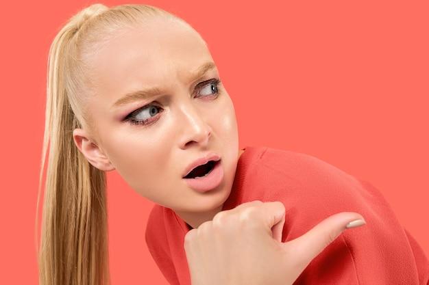 Jonge blonde verraste vrouw op koraalachtergrond