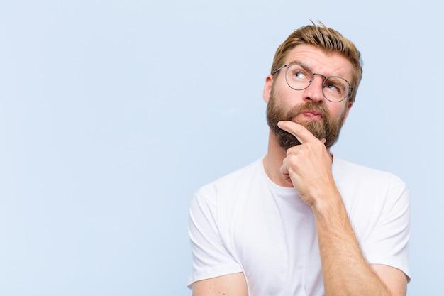 Jonge blonde volwassen man denkt, twijfelachtig en verward, met verschillende opties, zich afvragend welke beslissing hij moet nemen