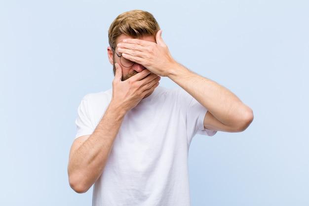 Jonge blonde volwassen man die gezicht bedekt met beide handen nee zeggen tegen de camera! afbeeldingen weigeren of foto's verbieden