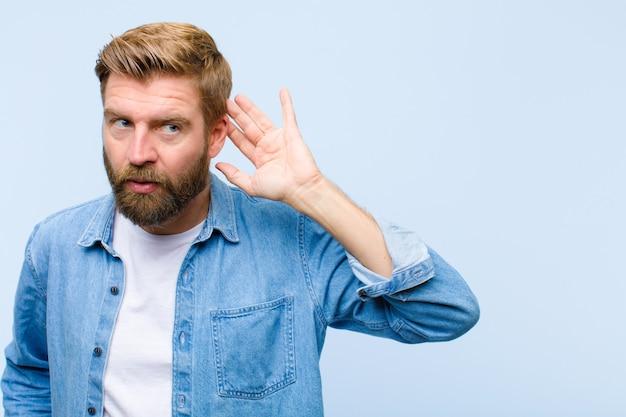 Jonge blonde volwassen man die lacht, nieuwsgierig naar de zijkant kijkt, probeert te luisteren naar roddel of een geheim afluistert