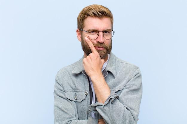 Jonge blonde volwassen man die serieus, attent en wantrouwend kijkt, met één arm gekruist en hand op kin, wegingsopties