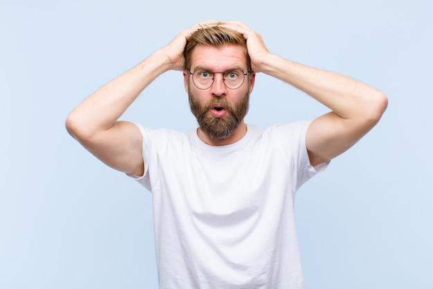 Jonge blonde volwassen man die zich geschokt en geschokt voelt, handen opheft en in paniek raakt bij een fout