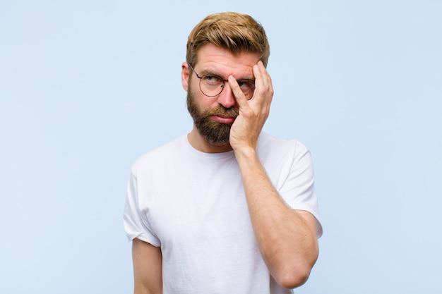 Jonge blonde volwassen man die zich verveeld, gefrustreerd en slaperig voelt na een vermoeiende, saaie en vervelende taak, gezicht met hand vasthouden