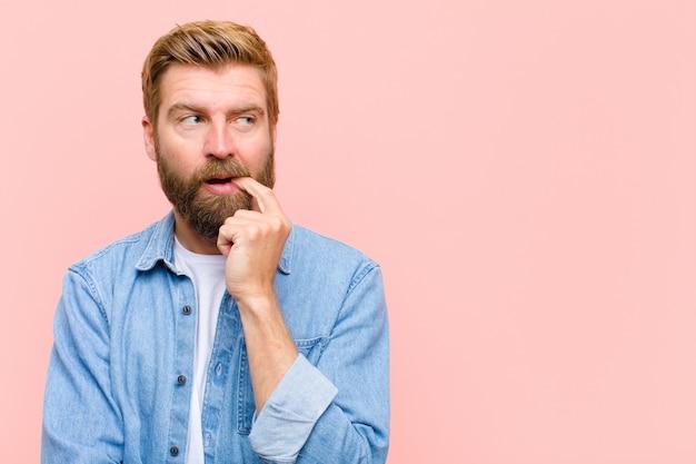 Jonge blonde volwassen man met verbaasde, nerveuze, bezorgde of bange blik, kijkend naar de kant naar kopie ruimte