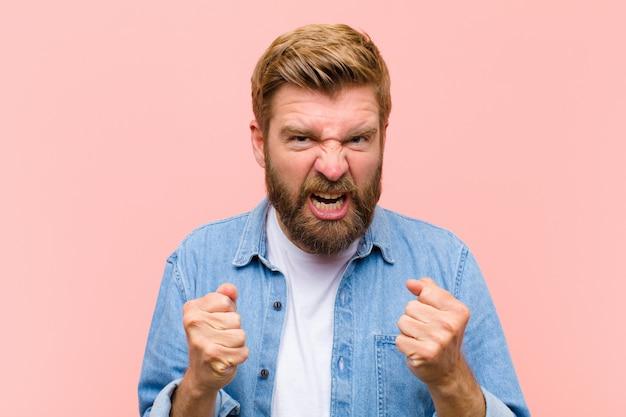 Jonge blonde volwassen man schreeuwt agressief met geïrriteerde, gefrustreerde, boze blik en strakke vuisten, woedend