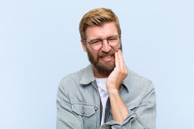 Jonge blonde volwassen man wang houden en lijden aan pijnlijke kiespijn, ziek, ellendig en ongelukkig voelen, op zoek naar een tandarts