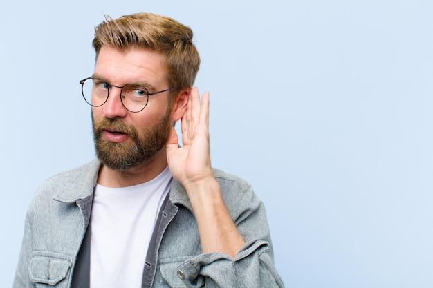 Jonge blonde volwassen mens die ernstig en nieuwsgierig kijkt, luistert, probeert een geheim gesprek te horen of roddel, afluisterend