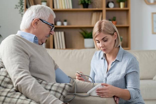Jonge blonde voorzichtige vrouw met tonometer die de bloeddruk van haar bejaarde zieke vader thuis meet