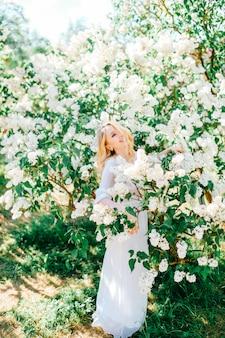 Jonge blonde vrolijke vrouw portret in lila struiken