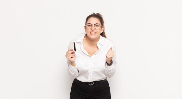 Jonge blonde vrouw agressief schreeuwen met een boze uitdrukking of met gebalde vuisten vieren succes