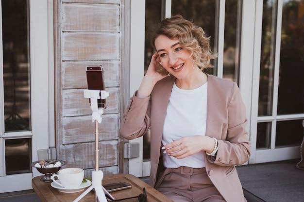 Jonge blonde vrouw blogger werkt in een straatcafé op een mobiele telefoon