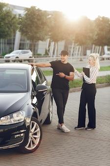 Jonge blonde vrouw consultant toont de klant de auto buiten. een man koopt een auto. maak een proefrit in een nieuwe auto.