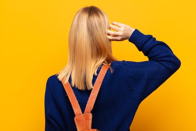 Jonge blonde vrouw denken of twijfelen, hoofd krabben, zich verbaasd en verward voelen, achter- of achteraanzicht