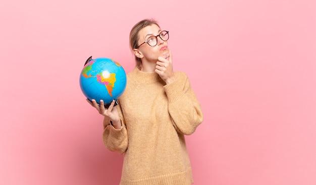 Jonge blonde vrouw denkt, voelt zich twijfelachtig en verward, met verschillende opties, zich afvragend welke beslissing ze moet nemen. wereld concept