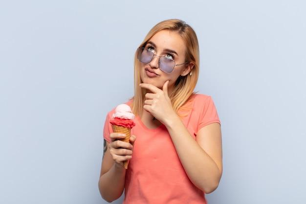 Jonge blonde vrouw denkt, voelt zich twijfelachtig en verward, met verschillende opties, zich afvragend welke beslissing ze moet nemen