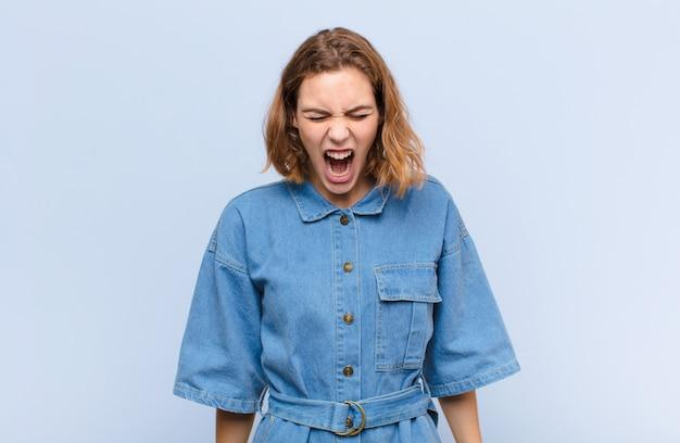 Jonge blonde vrouw die agressief schreeuwt, erg boos, gefrustreerd, verontwaardigd of geïrriteerd, nee schreeuwend tegen een egale kleurenmuur