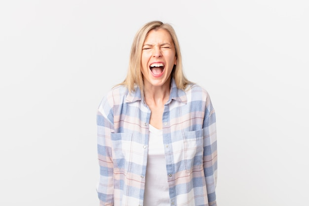 Jonge blonde vrouw die agressief schreeuwt, erg boos kijkt
