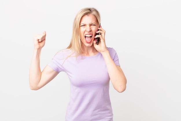 Jonge blonde vrouw die agressief schreeuwt met een boze uitdrukking en belt met een smartphone