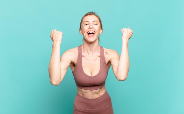 Jonge blonde vrouw die agressief schreeuwt met een boze uitdrukking of met gebalde vuisten om succes te vieren. sport concept