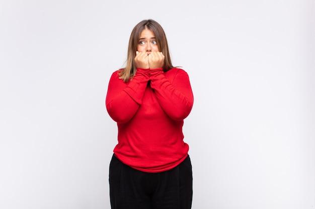 Jonge blonde vrouw die bezorgd, angstig, gestrest en bang kijkt, vingernagels bijt en op zoek is naar zijdelingse kopieerruimte