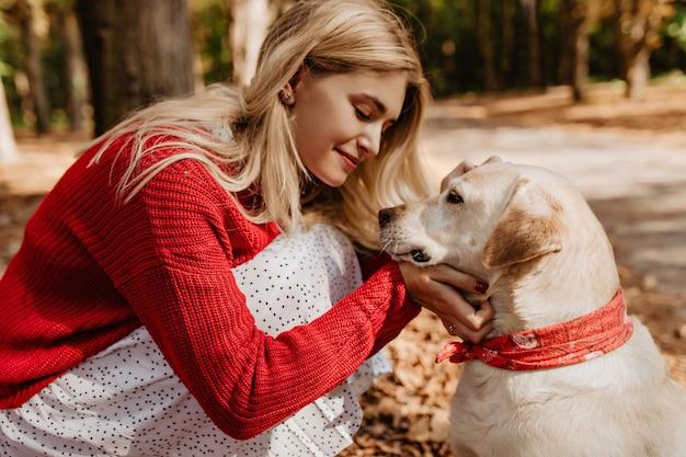 Jonge blonde vrouw die bij haar hond glimlacht. mooi meisje dat goede momenten deelt met een huisdier in het park.
