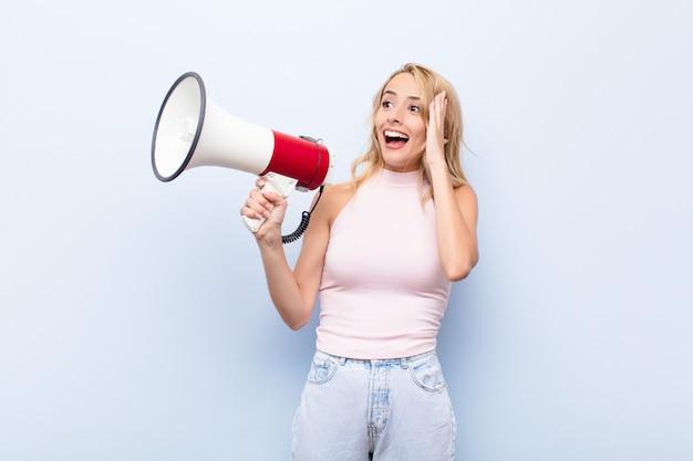 Jonge blonde vrouw die blij, opgewonden en verrast voelt, naar de zijkant kijkend met beide handen op het gezicht met een megafoon
